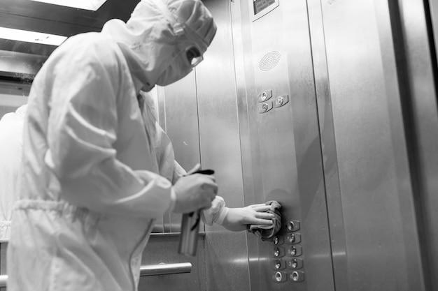 Koronawirus infekcja. sanitariusz w masce ochronnej i kostiumu dezynfekującym windę za pomocą opryskiwacza,