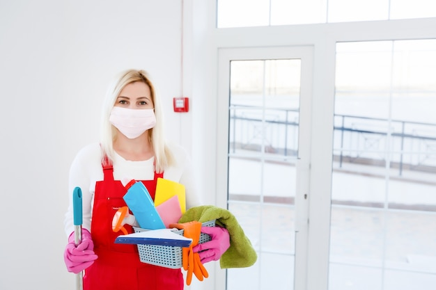 Koronawirus. kobieta z maseczką myjąca i dezynfekująca swój dom podczas epidemii koronawirusa. zapobieganie zakażeniu covid-19. powstrzymaj rozprzestrzenianie się koronawirusa.