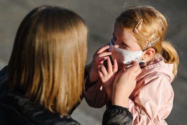 Koronawirus koncepcja końcowa. nigdy więcej covid-19. mała dziewczynka, matki noszą maski chodzą po ulicy. mama usuwa maskę szczęśliwe dziecko. rodzina z dzieckiem na zewnątrz. świętować sukces. pandemia się skończyła, skończyła się.