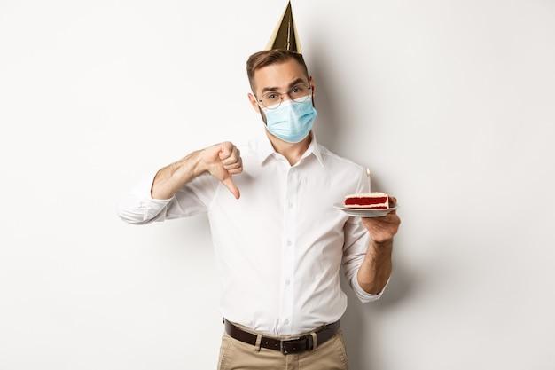 Koronawirus, kwarantanna i święta. mężczyzna pokazuje kciuk w dół jako rozczarowany przyjęciem urodzinowym, ma na sobie maskę i trzyma tort urodzinowy, białe tło.