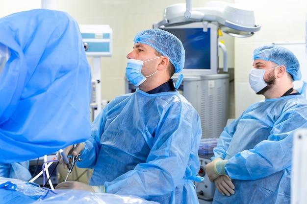 Koronawirus. lekarze i pielęgniarki pracujące w szpitalach. walka z koronawirusem. mężczyzna lekarz w kombinezonie ochronnym i masce patrząc na ekran. szczepionka. bohaterowie.