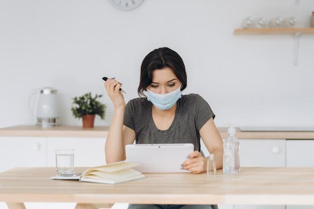 Koronawirus. młoda biznesowa kobieta pracuje od domu jest ubranym ochronną maskę. dziewczyna w kwarantannie na koronawirusa w masce ochronnej. praca w domu z żelem dezynfekującym i wodą