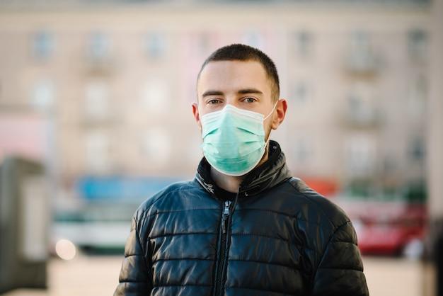 Koronawirus. młody mężczyzna na ulicy miasta w masce ochronnej przed rozprzestrzenianiem się choroby covid-19. przeciwko sars-cov-2. pandemiczny. epidemia. chroń swoje zdrowie. pojęcie kwarantanny.