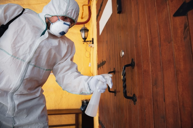 Koronawirus pandemia. dezynfektor w kombinezonie ochronnym i masce rozpyla środki dezynfekujące w domu lub biurze. ochrona przed chorobą covid-19. zapobieganie rozprzestrzenianiu się wirusa zapalenia płuc na powierzchniach.