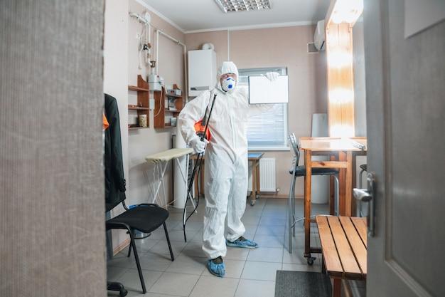 Koronawirus pandemia. dezynfektor w kombinezonie ochronnym i masce rozpyla środki dezynfekujące w domu lub biurze