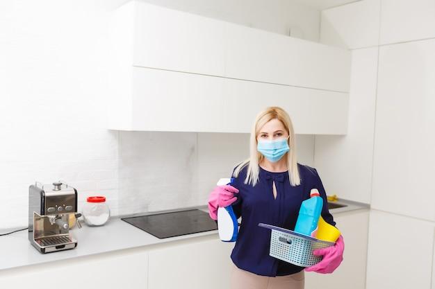 Koronawirus pandemia. dezynfektor w masce ochronnej rozpyla środki dezynfekujące w pomieszczeniu. zapobieganie chorobie koronawirusowej. czyszczenie i dezynfekcja środowiska podczas epidemii koronawirusa