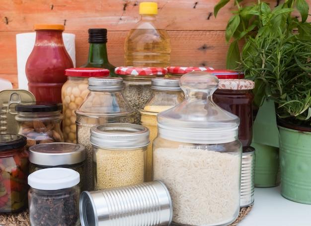 Koronawirus pandemia. mała podaż żywności na okres izolacji w kwarantannie. szklane słoiki ze zbożami, strączkami, dżemami, makaronem i ryżem, puszki w puszkach