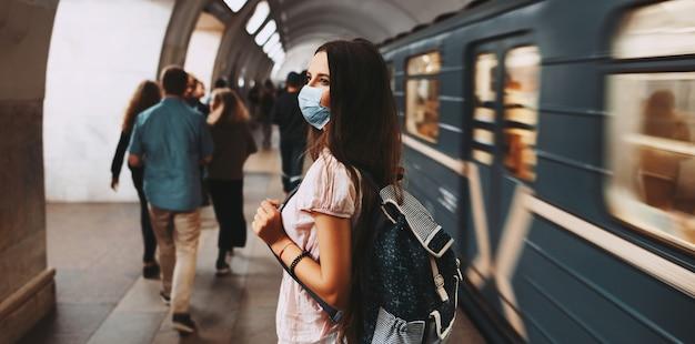 Koronawirus pandemia. widok młodej dziewczyny z plecakiem, noszącej ochronną maskę medyczną z tyłu