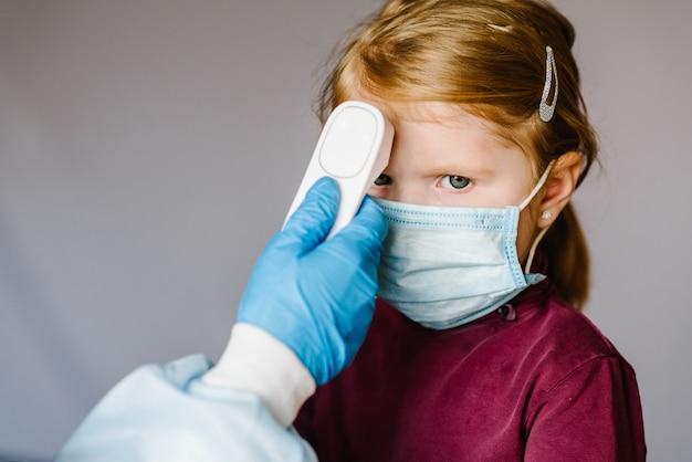 Koronawirus. pielęgniarka lub lekarz sprawdza temperaturę ciała dziewczyny za pomocą termometru na czoło na podczerwień (pistolet) w celu wykrycia wirusa - koncepcja epidemii. wysoka temperatura.