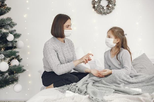 Koronawirus u dziecka. matka z córką. dziecko leżące w łóżku. kobieta w masce medycznej.
