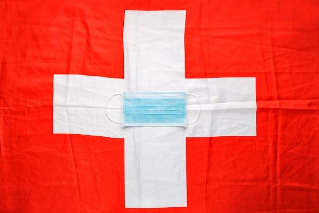 Koronawirus w szwajcarii. ochronna chirurgiczna maska na twarz na szwajcarskiej fladze narodowej.