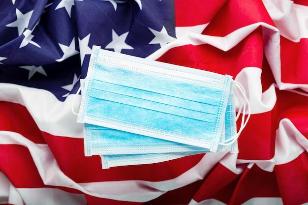 Koronawirus w usa. ochronna chirurgiczna maska na amerykańską flagę narodową. koronawirus flagi amerykańskiej i zapobieganie zakażeniom wirusowym, covid-19