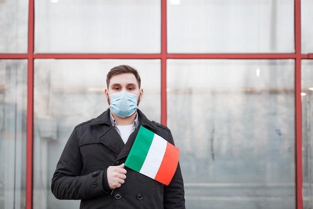 Koronawirus włoch rozprzestrzenia się. mężczyzna w masce medycznej, maska ochronna z włoską flagą.
