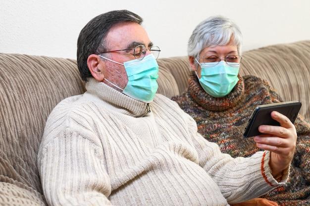 Koronawirus. zostań w domu, styl życia. rozochocone starsze osoby dobierają się obsiadanie na kanapie na kwarantannie w domu, robić rozmowie wideo z smartphone. starsza para jest ubranym maski ochronne.