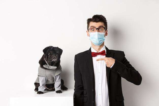 Koronawirus, zwierzęta i koncepcja uroczystości. zdziwiony młody człowiek w masce i garniturze, wskazując na ślicznego czarnego psa siedzącego obok właściciela w imprezowym stroju, biały.