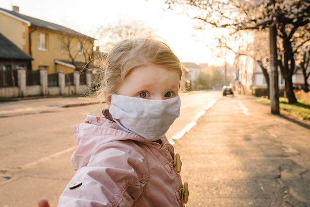 Koronawirusy i epidemiczne choroby wirusowe. zdrowe dziecko w medycznych maski ochronne na ulicy. ochrona zdrowia i zapobieganie podczas grypy i epidemii zakaźnej. zostań w domu, ocal swoje życie.
