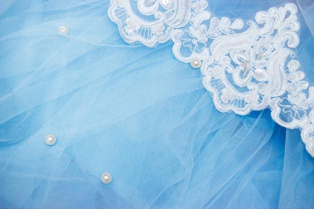 Koronka na niebieskim tiulu z koralikami. szycie sukni ślubnej. koncepcja ślubu