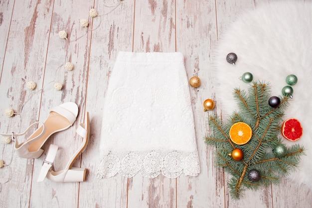 Koronkowa biała spódnica i białe buty na drewnianym tle, bombki na gałęzi jodły. modna koncepcja, widok z góry