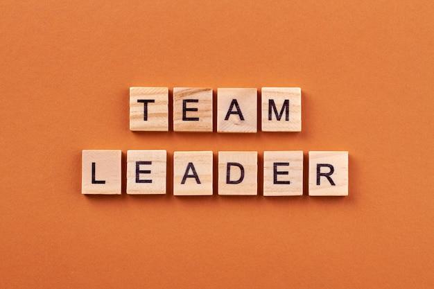 Korporacyjna koncepcja przywództwa. tekst lidera zespołu na drewnianych kostkach na białym tle na pomarańczowym tle.