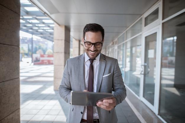 Korporacyjny biznesmen używa pastylkę dla sprawdzać emaila podczas gdy stojący przed sklepowym okno. portret w pasie.