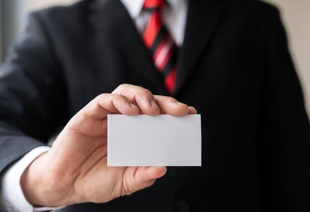 Korporacyjny mężczyzna trzyma pustą wizytówkę