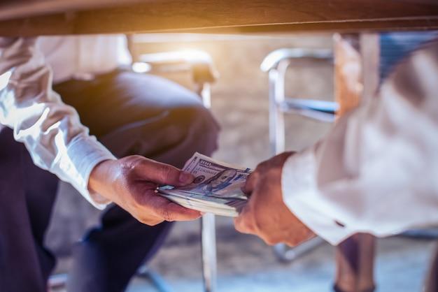 Korupci pojęcie, biznesmen bierze łapówkę od mężczyzna pod stołem