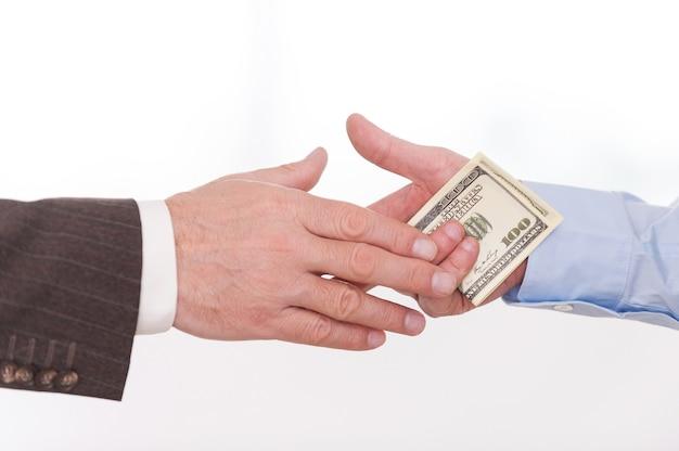 Korupcja. zbliżenie: biznesmen dający pieniądze innemu mężczyźnie podczas uścisku dłoni