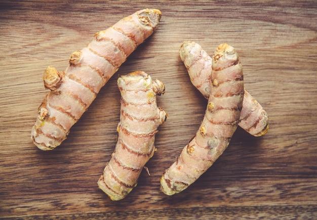 Korzeń kurkumy na drewnianej desce do krojenia