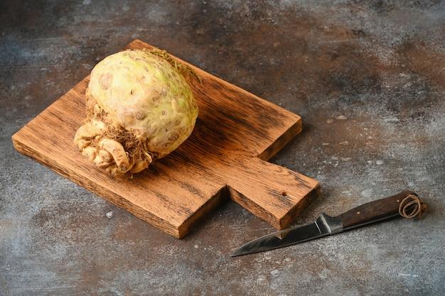 Korzeń selera na drewnianej desce do krojenia.