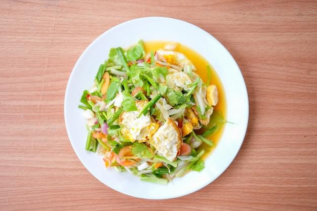 Korzenna sałatka z smażonymi jajkami (yam kai dao) służy na białym naczyniu ustawionym na brązowym stole - domowej roboty karmowy pojęcie.