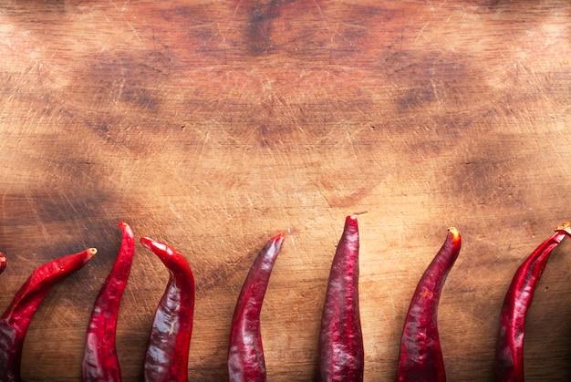 Korzenni chili pepers na drewnianym tle, odgórny widok