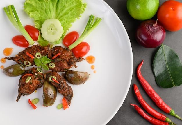 Korzenny smażący fertanie sum na bielu talerzu, tajlandzki jedzenie.