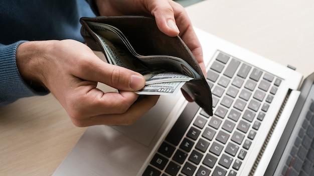 Korzyści finansowe z pracy w firmie it. człowiek posiadający pieniądze dolarów. technologie internetowe tworzenie oprogramowania, aplikacje, koncepcja programowania