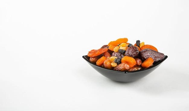 Korzyści i szkody suszonych owoców mieszanka suszonych owoców w talerzu na białym tle
