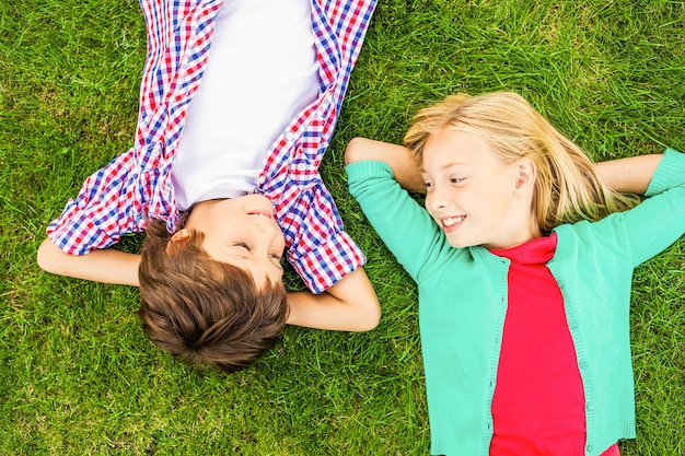 Korzystając z czasu letniego. widok z góry dwóch uroczych małych dzieci trzymających się za ręce za głową i patrzących na siebie z uśmiechem, leżących razem na zielonej trawie