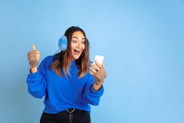 Korzystam z telefonu, szczęśliwy. portret kobiety rasy kaukaskiej na niebieskim tle studio. piękne modelki w ciepłych ubraniach. pojęcie ludzkich emocji, wyraz twarzy, sprzedaż, reklama. zimowy nastrój, wakacje.