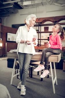 Korzystanie z fiszek. kochająca babcia używa fiszek podczas nauki z małą zabawną i ciekawską dziewczynką