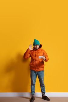 Korzystanie z gadżetów w dowolnym miejscu. młody człowiek kaukaski za pomocą smartfona, poddanie się, rozmowy, zakłady. portret pełnej długości na białym tle na żółtej ścianie. pojęcie nowoczesnych technologii, millenialsów, social media.