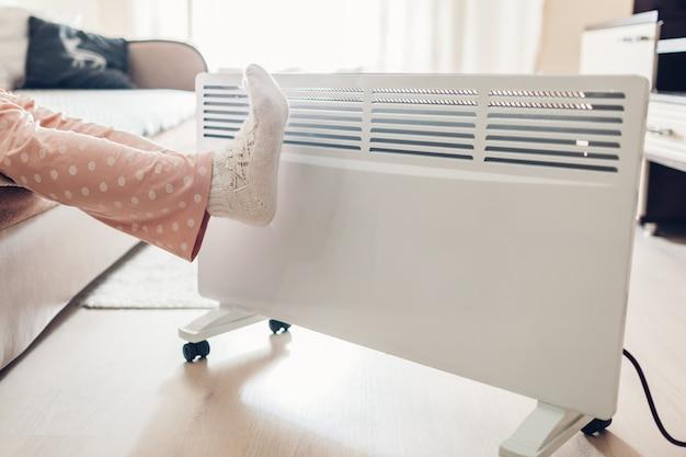 Korzystanie z grzejnika w domu w zimie. kobieta ocieplenie stóp. sezon grzewczy.