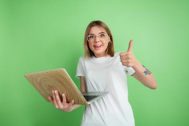 Korzystanie z laptopa emocjonalnego. kaukaski portret młodej kobiety na białym tle na zielonej ścianie. piękne modelki w białej koszuli. pojęcie ludzkich emocji, wyraz twarzy, młodość.