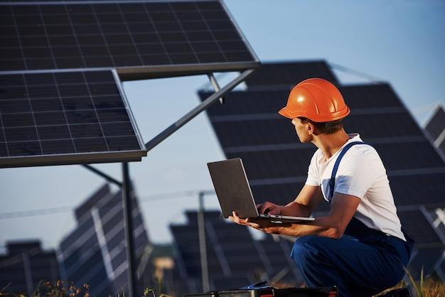 Korzystanie z laptopa. mężczyzna pracownik w niebieskim mundurze na zewnątrz z bateriami słonecznymi w słoneczny dzień.