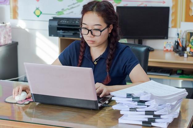 Korzystanie z laptopa przez kobietę, mysz bezprzewodową, przeglądanie stron internetowych w internecie lub wyszukiwanie pracy