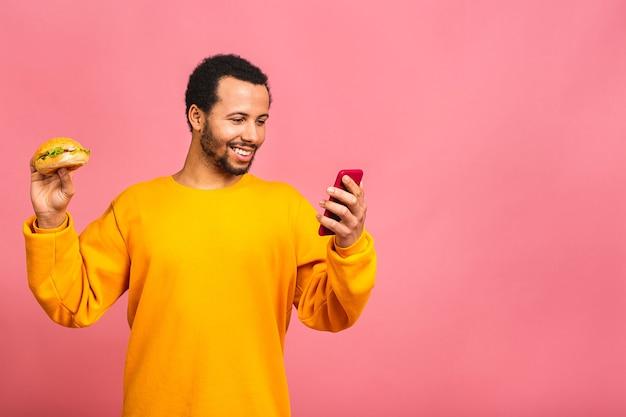 Korzystanie z telefonu komórkowego. młody człowiek jedzenie hamburgerów na białym tle nad różowym
