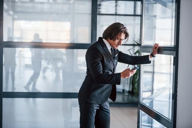 Korzystanie z telefonu. portret przystojny młody biznesmen w czarnym garniturze i krawat.
