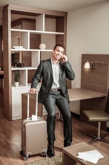 Korzystanie ze słuchawek. biznesmen używając słuchawek, dzwoniąc do żony po locie i przyjeżdżając do hotelu