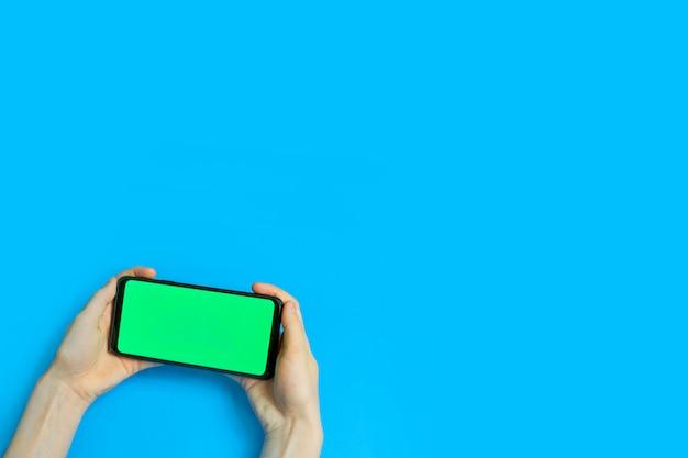 Korzystanie ze smartfona z zielonym ekranem. ręce przewijanie stron, dotykając ekranu dotykowego. widok z góry. kluczowanie kolorem