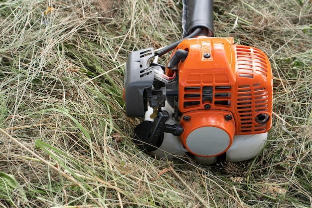 Kosa spalinowa z kosą spalinową leży na siano skoszonym po skoszeniu wysokiej trawy w ogrodzie wiejskiego domu