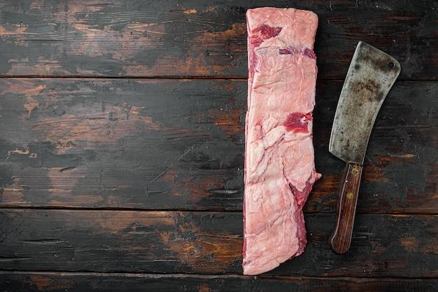Kość krótkie żeberka w zestawie gulaszowym i starym nożem rzeźniczym, na starym ciemnym drewnianym stole tle, widok z góry płasko leżący, z miejscem na kopię na tekst