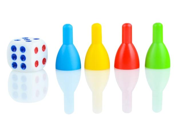Kości dla dzieci i szpilki do kręgli w różnych kolorach na białym tle.