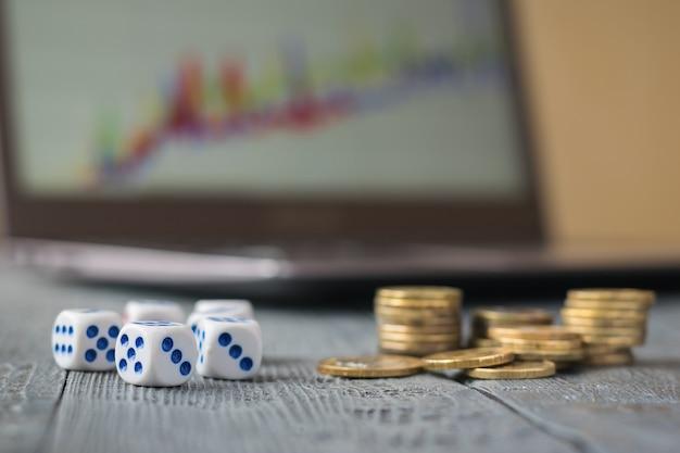 Kości i stos monet przed laptopem z harmonogramami biznesowymi na ciemnym stole.